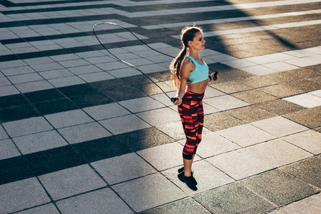 Sportswoman skipping ropes outdoors