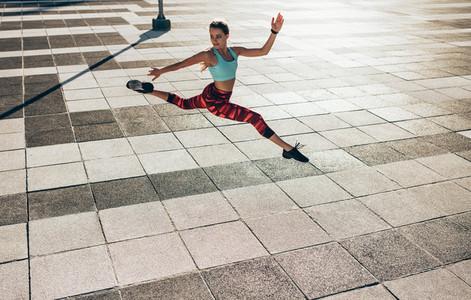 Fitness woman doing split jump
