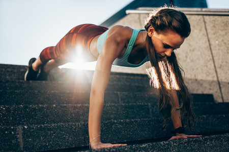 Sportswoman doing push ups on steps