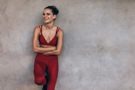 Smiling sportswoman leaning to a grey wall