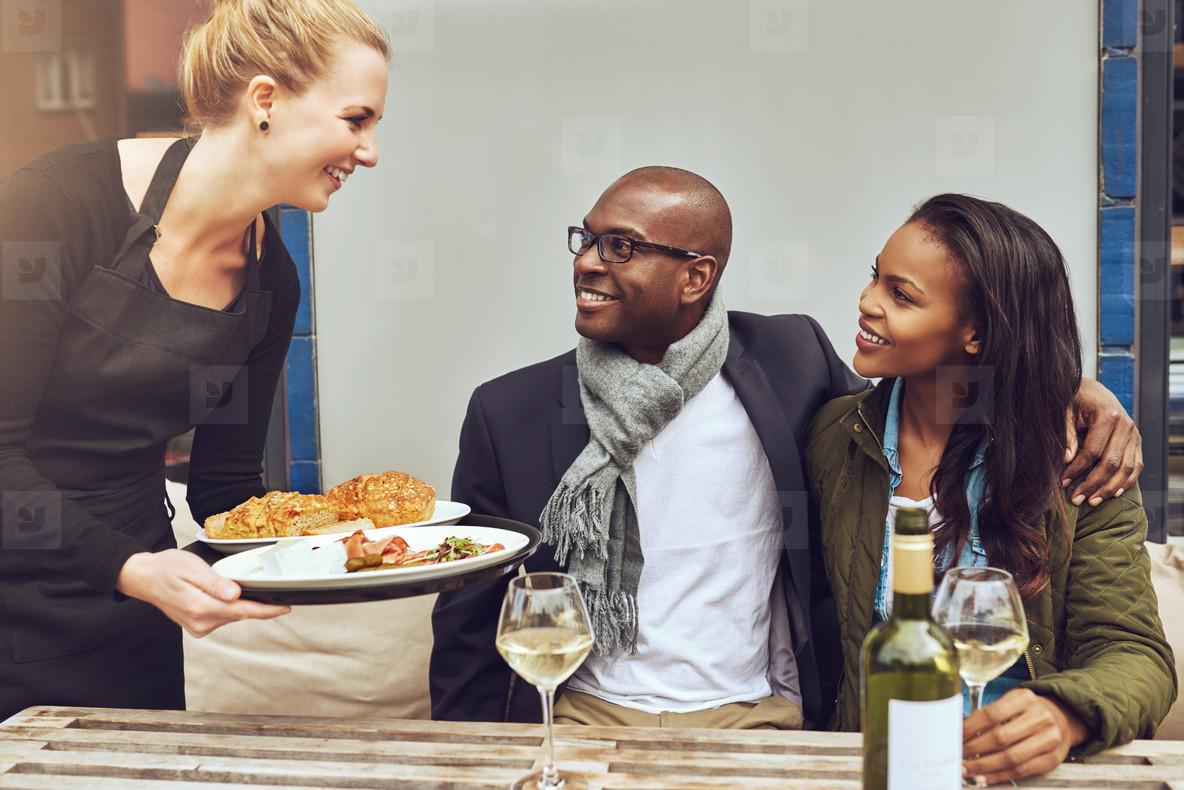 Waitress serving an African American couple dinner