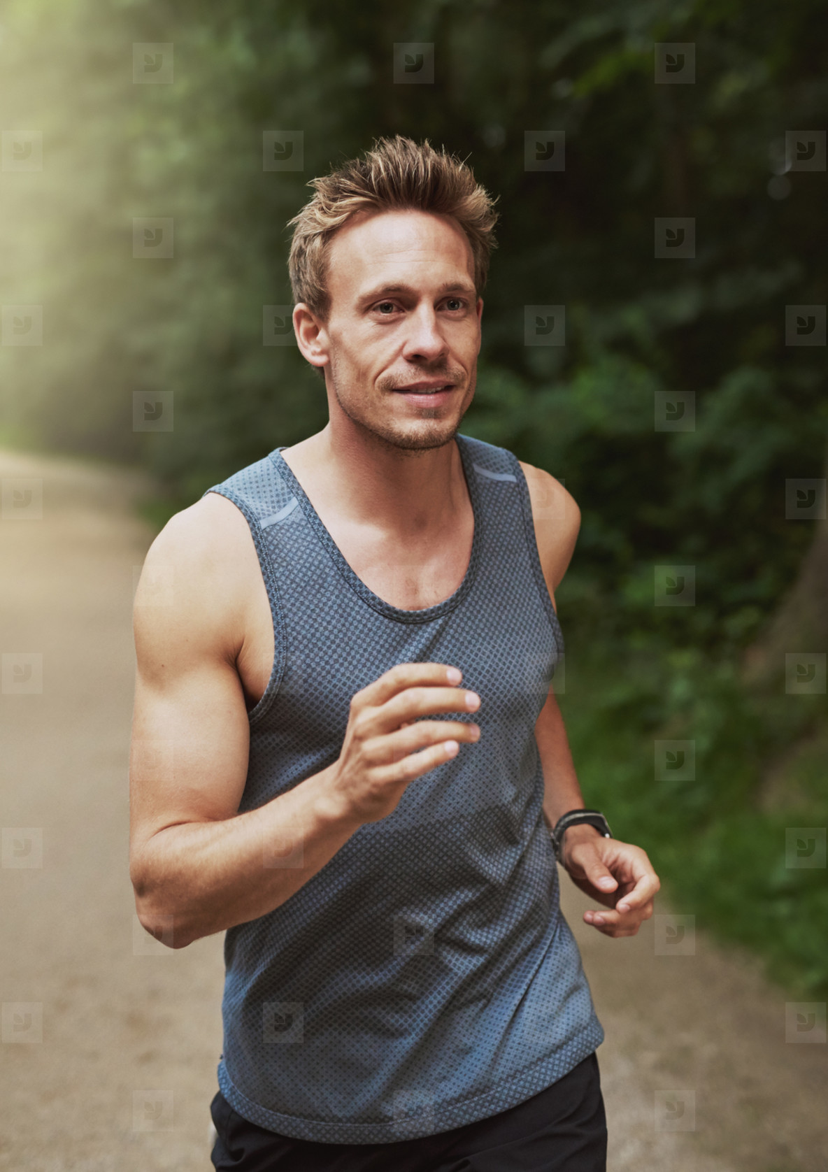 Portrait of young man running in forest