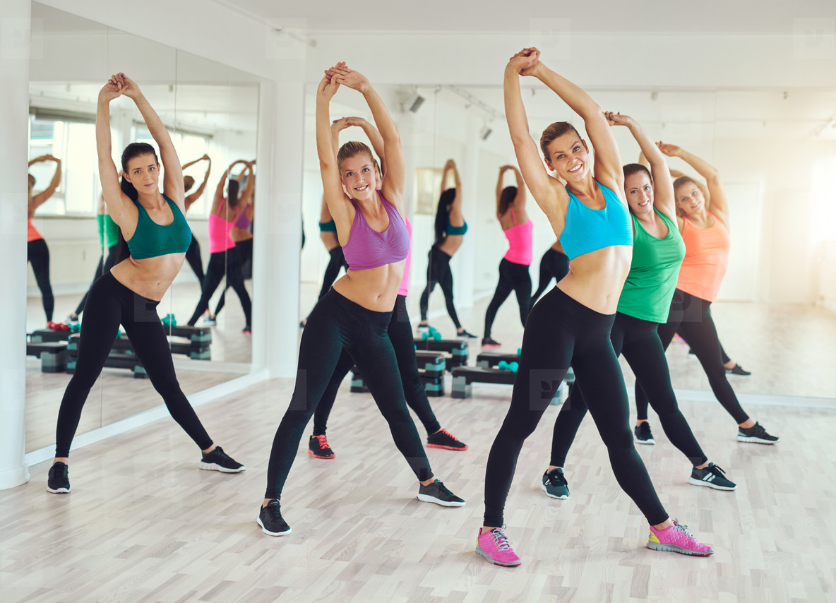 Group of young women looking at camera while doing exercise together