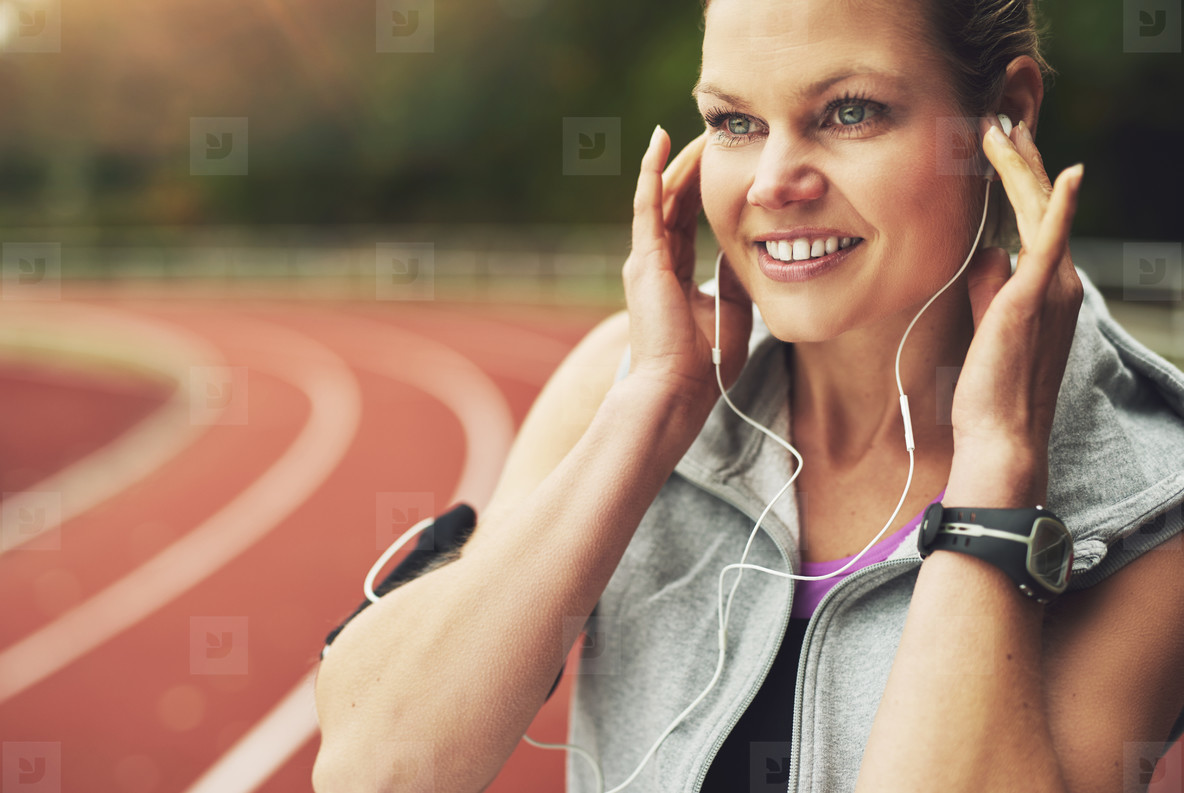 Close up of smiling female athlete listening to music