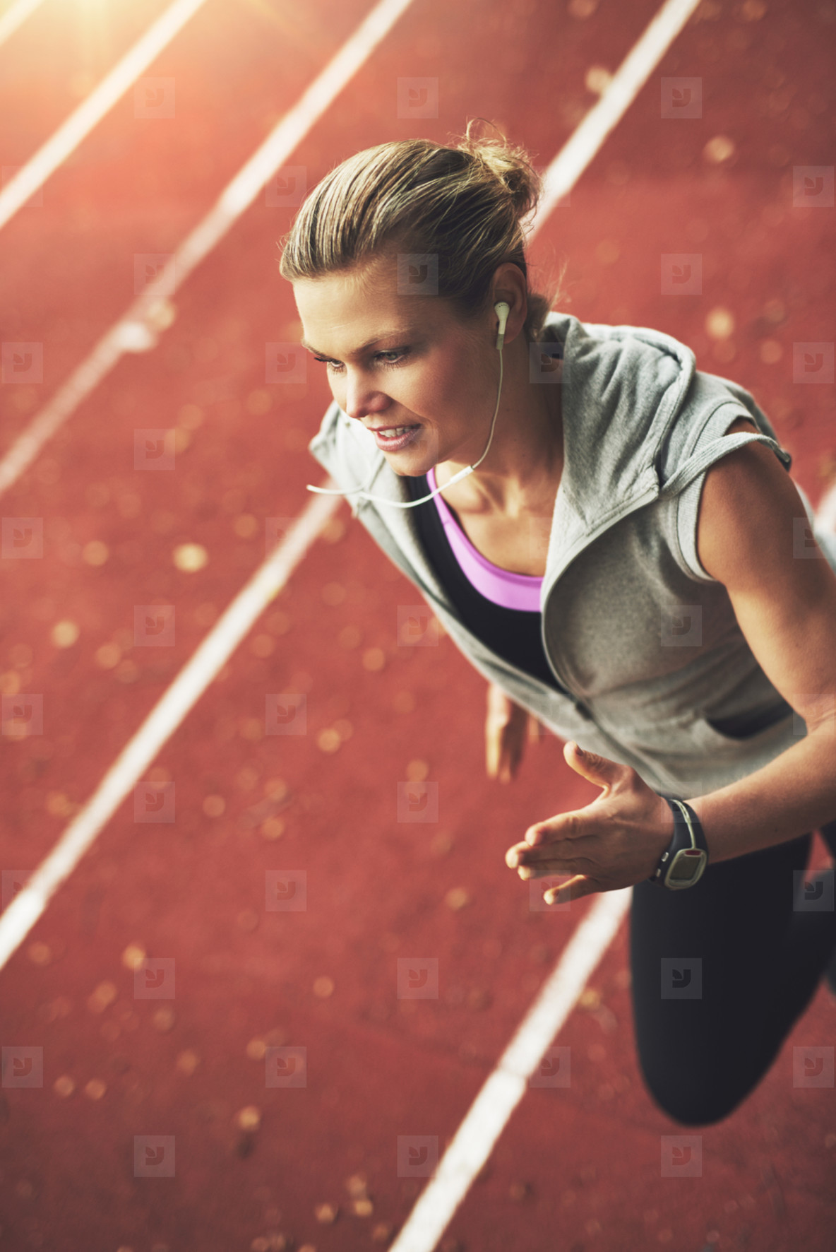 Close up of athletic young woman running fast on stadium