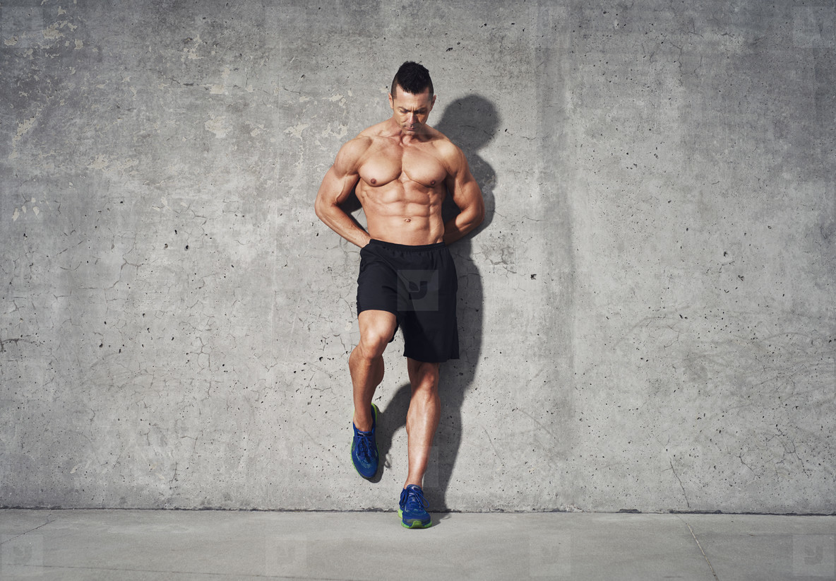 Fitness model standing against grey background