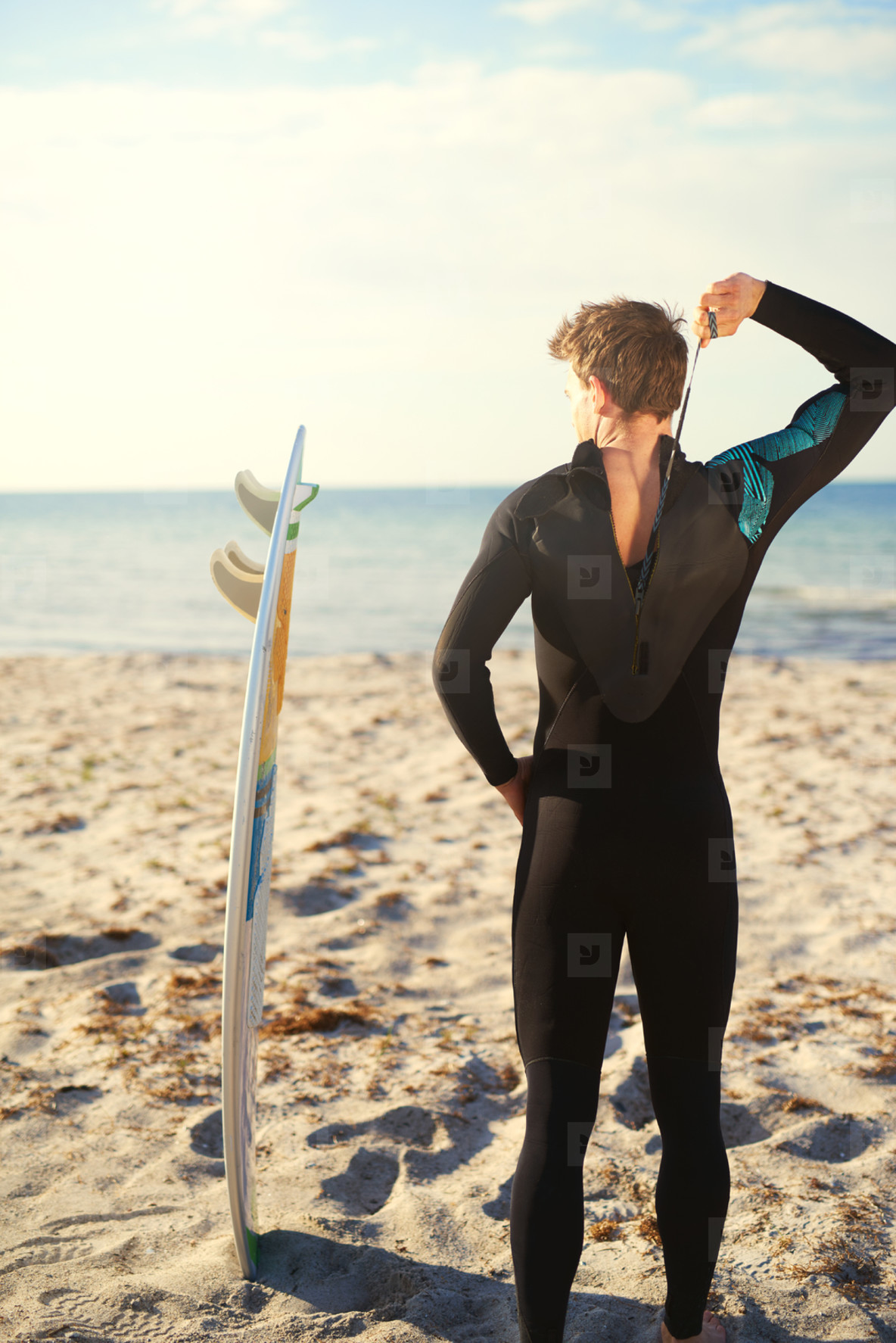 Surfer zipping up his wetsuit