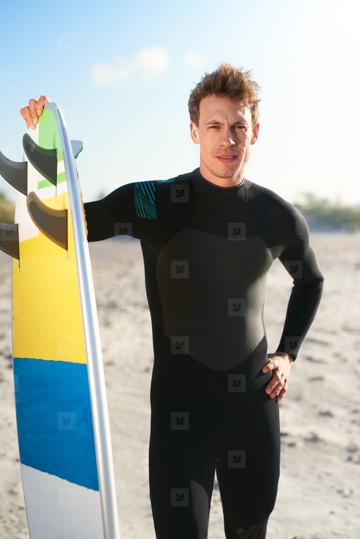 Handsome young surfer posing with his surfboard