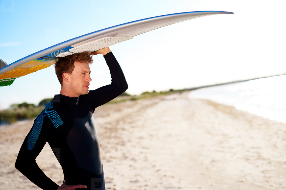 Attractive surfer balancing his board on his head