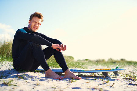 Male Surfer Sits Beside his Surfboard on the Sand
