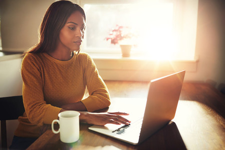 Woman working on laptop with bright sunlight