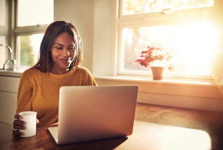 Laughing woman looking at laptop