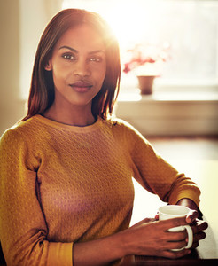 Calm black woman sitting at table with bright sun