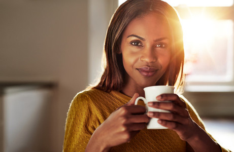 Smiling friendly young black woman drinking coffee