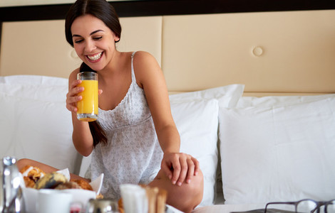 Woman laughing while holding glass of orange juice
