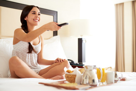 Woman relaxing in bed holding remote control