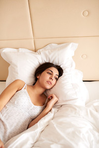 Woman lying in bed with head on pillow