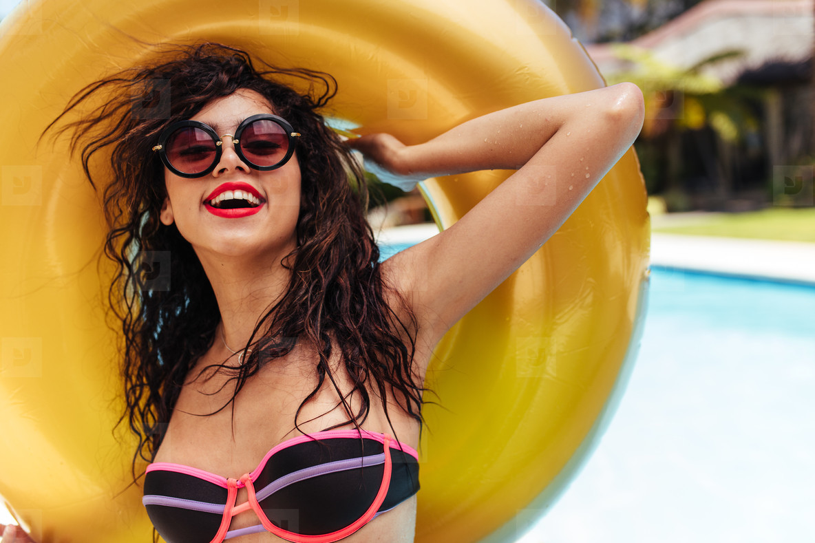 Woman in bikini posing with inflatable ring near pool