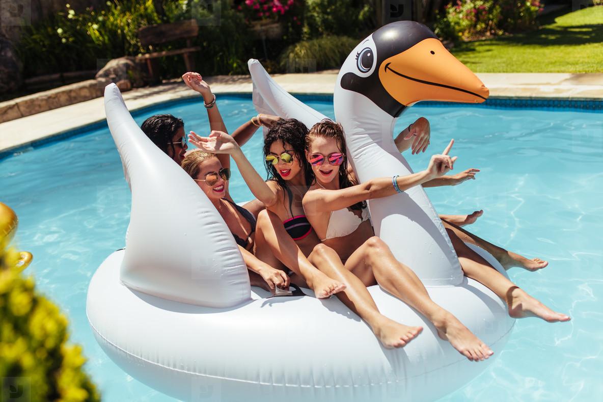 Girls having fun on floating toy in swimming pool