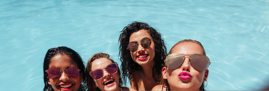 Girls posing for group selfie in pool