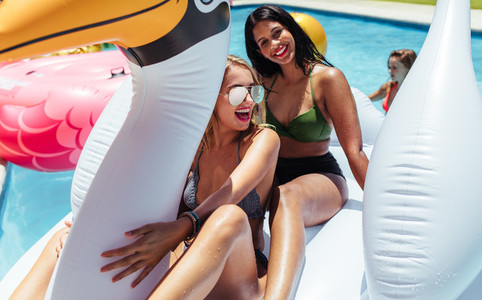 Girs having fun on an inflatable toy in pool