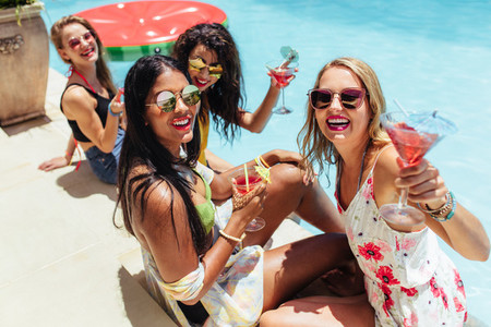 Girls enjoying a poolside party with cocktails
