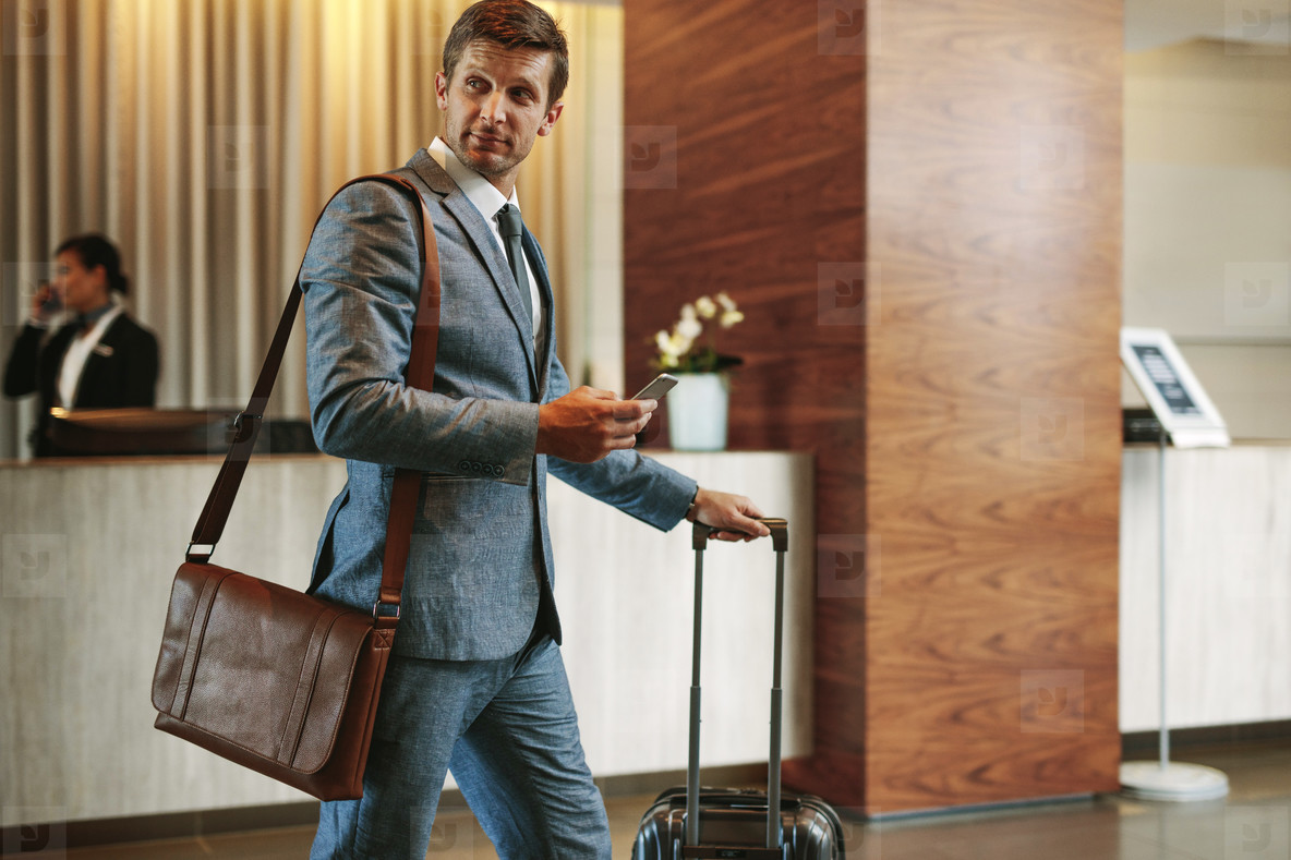 Businessman in hotel hallway with phone and baggage