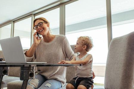 Busy woman with son in home office