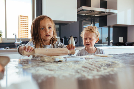 Children making cookies in kitchen