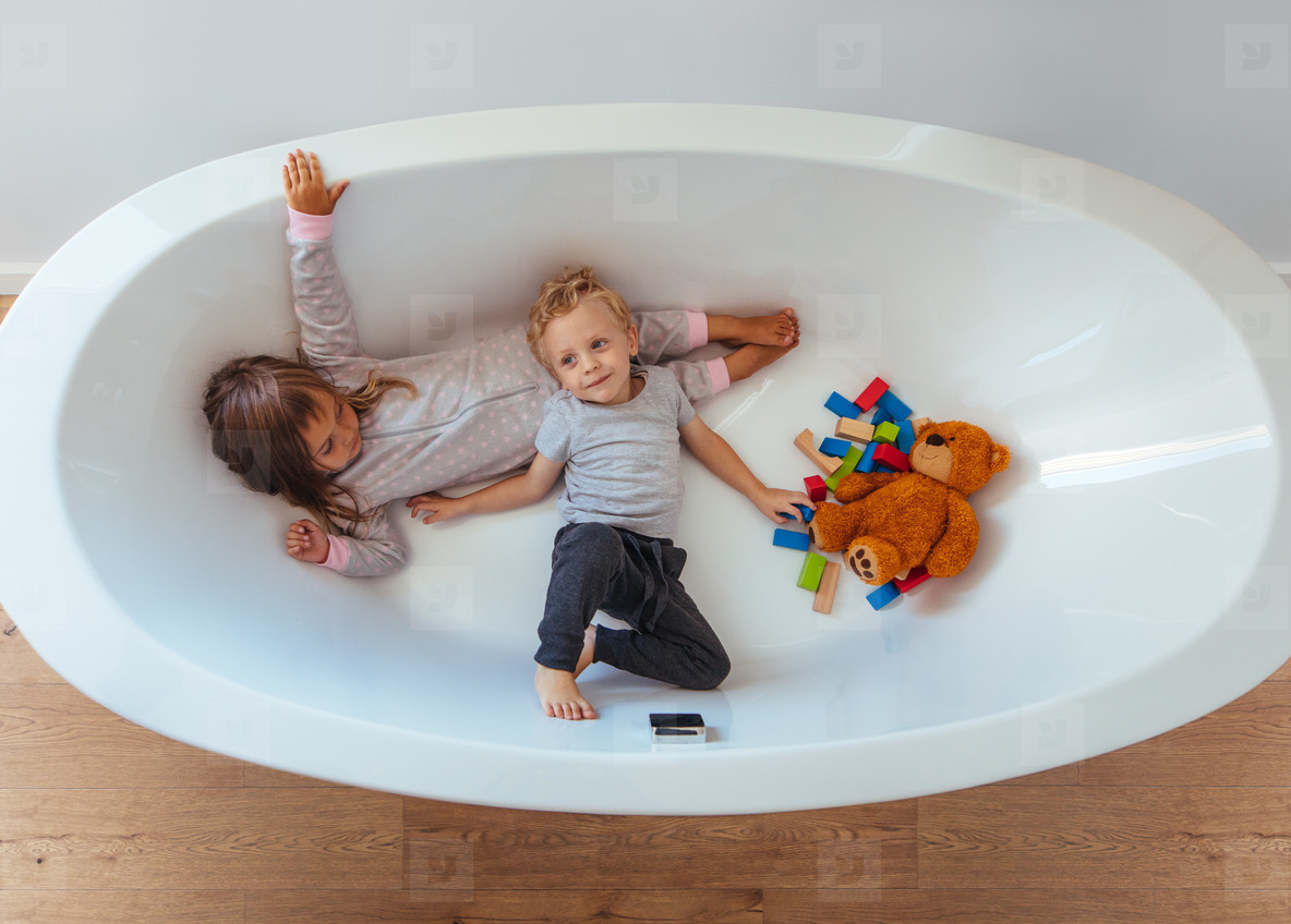 Little siblings playing inside a bathtub