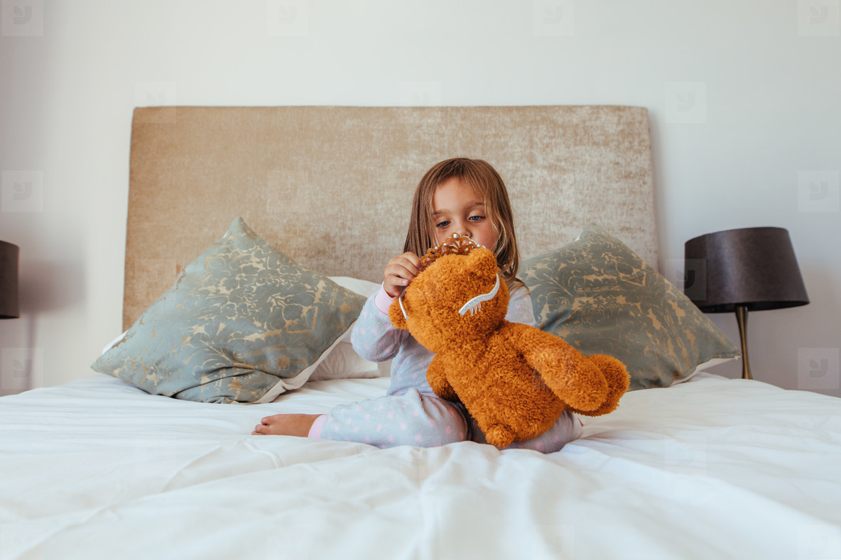 Cute little girl playing with a teddy bear