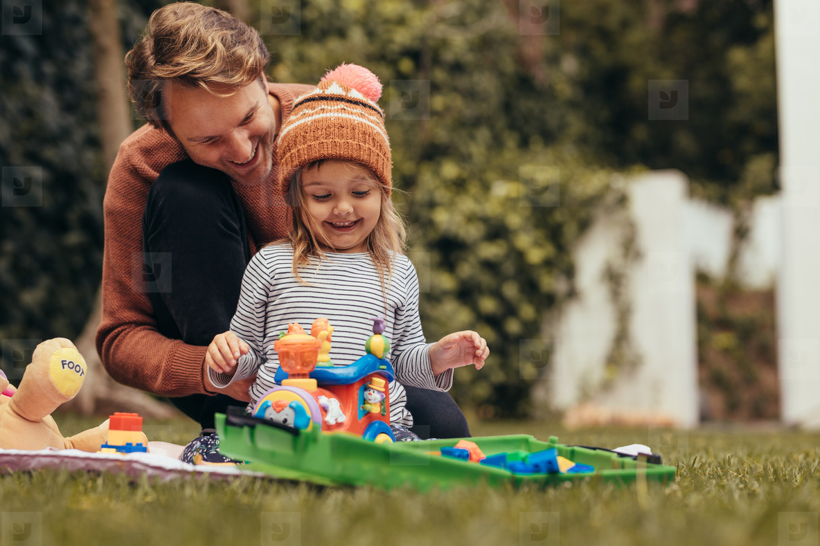 Father and daughter playing with toys in park