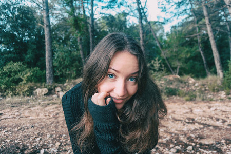 a girl with long hair and blue eyes in the mountains smiling