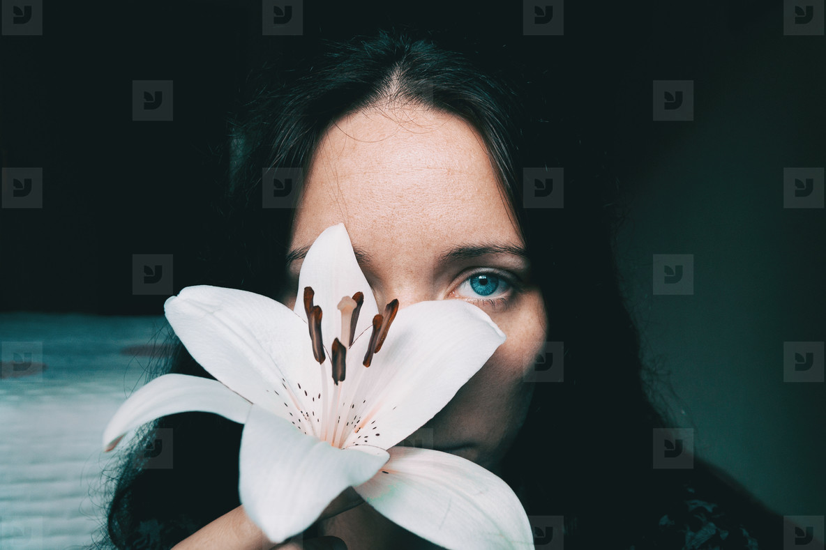 a girl with a white lily covering an eye