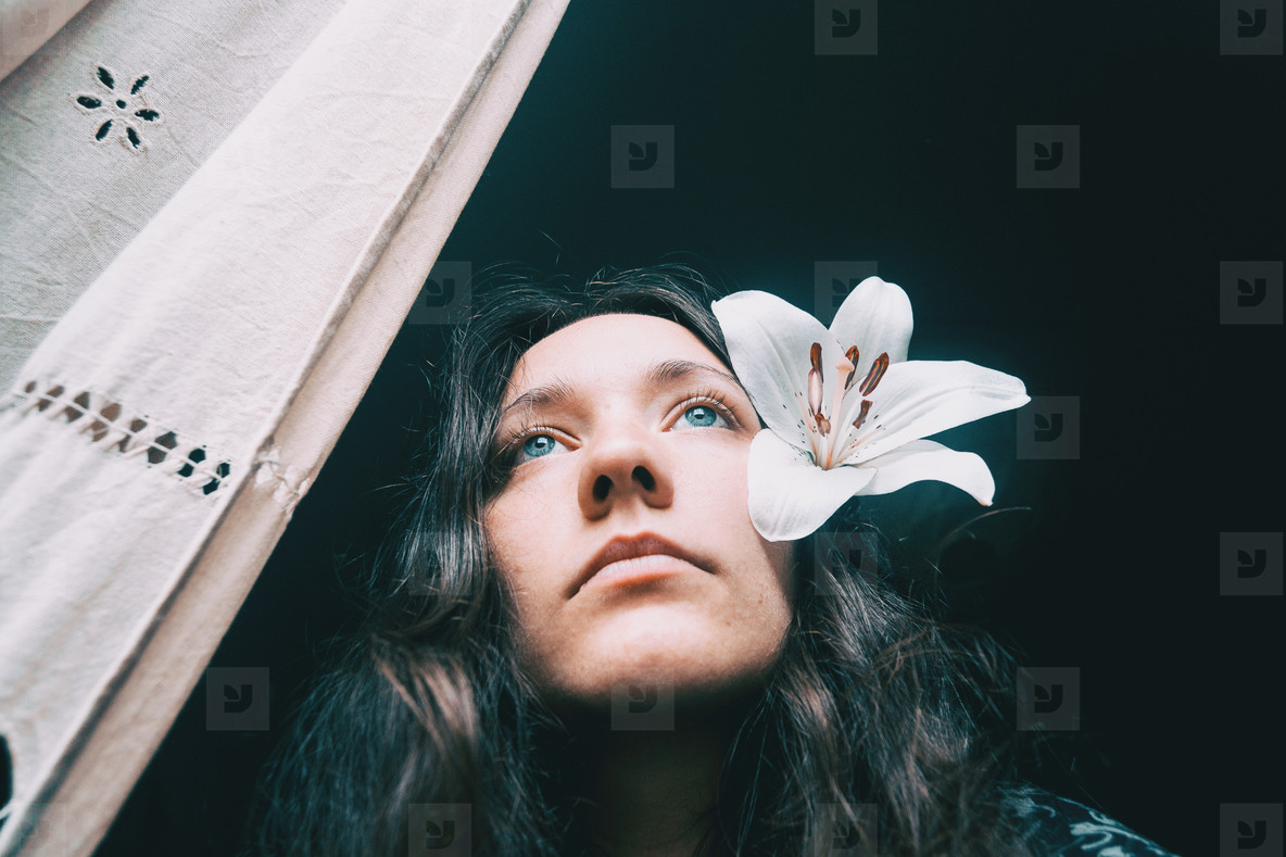 a girl with a white lily looking out the window