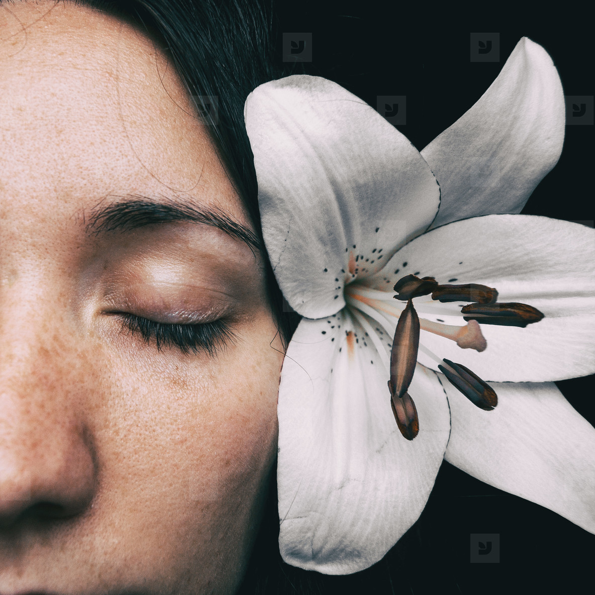 half of a girls face with a white lily and closed eyes