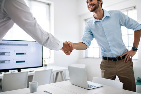 Business partners shaking hands in office