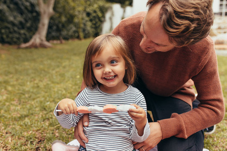 Little girl with her father outdoors holding a candy