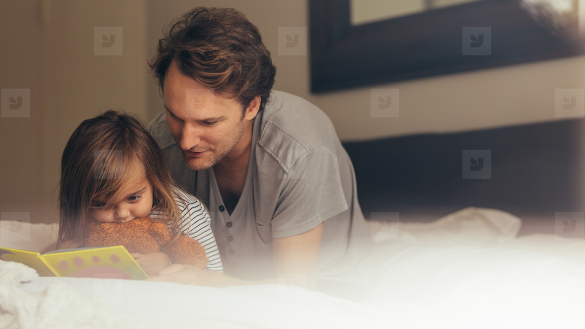 Father and daughter reading a story book