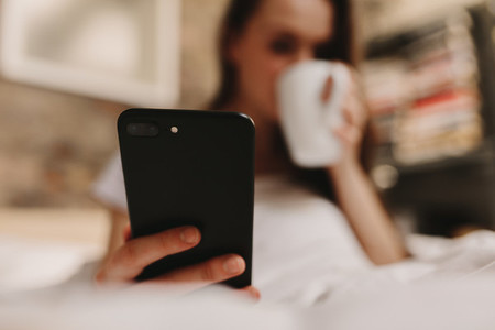 Woman drinking bed coffee looking at mobile phone