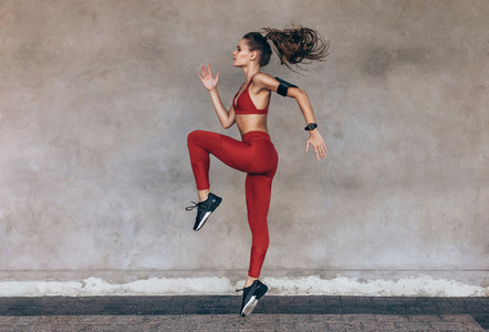 Sportswoman jumping and stretching