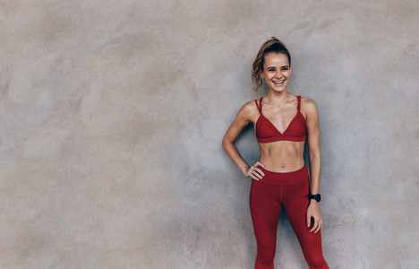 Sportswoman standing against a wall and smiling