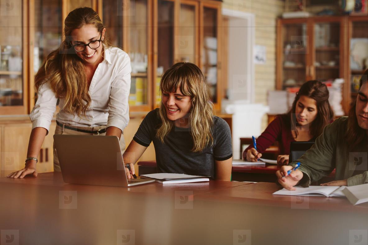 Teacher helping her student at high school