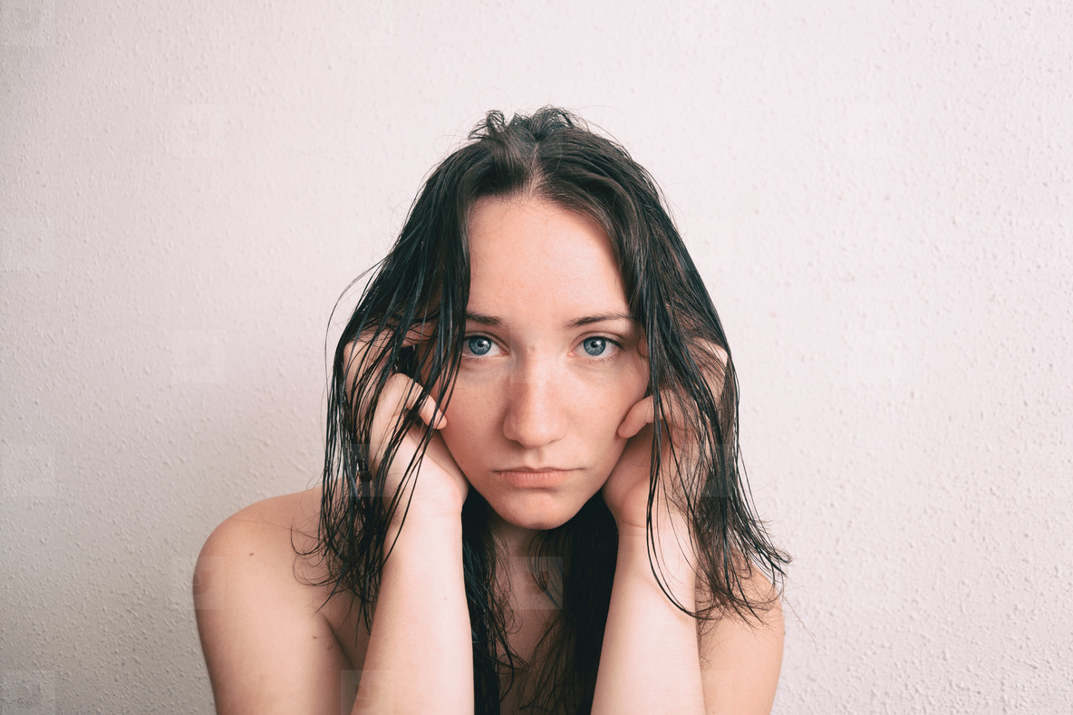 a long haired girl touching her face with her hands