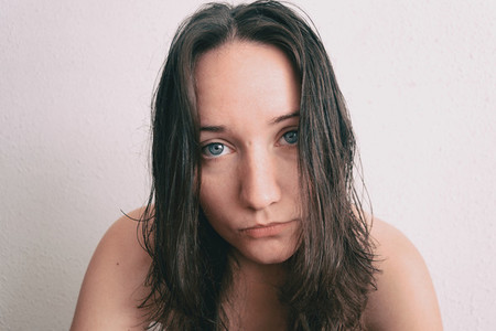 a girl with long hair and blue eyes looking at camera