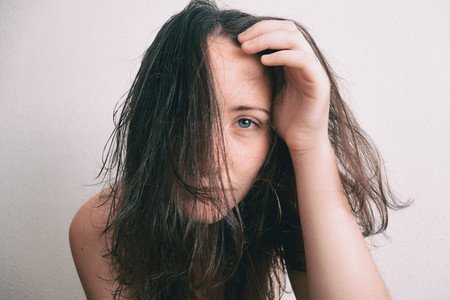 a girl with her face full of hair removing it with her hand