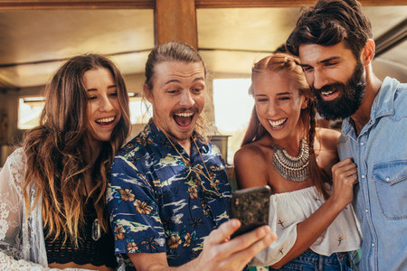 Laughing friends taking selfie with cellphone