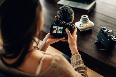Woman blogger looking at her camera