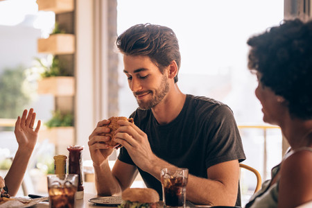 Man eating burger with friends at restaurant