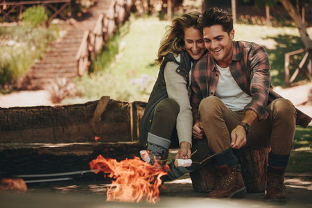 Smiling couple roasting sweets on bonfire